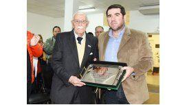 Eduardo Bernal recibe la placa de manos del director de Chubut Deportes