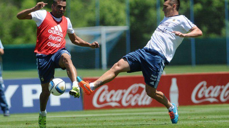 Gabriel Mercado disputando el balón con Matías Kranevitter durante el entrenamiento que la Selección realizó ayer en el predio Ezeiza.