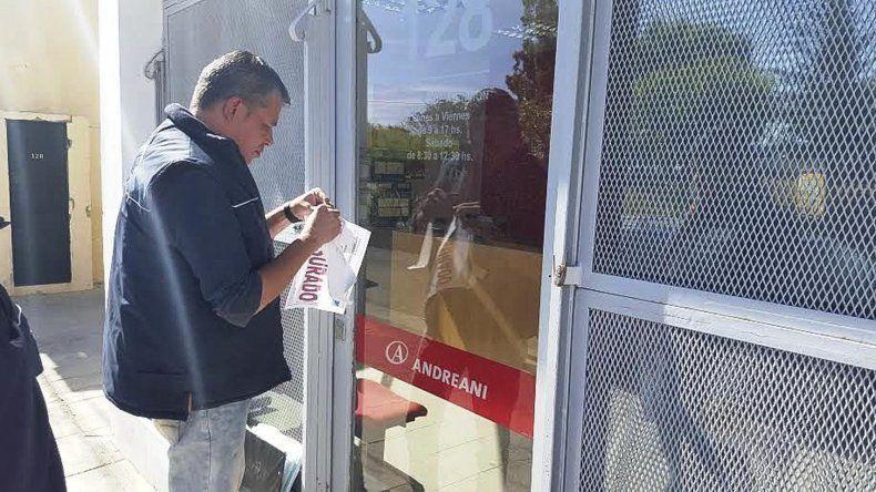 Los funcionarios colocan la faja de clausurado en las puertas del Correo Andreani.