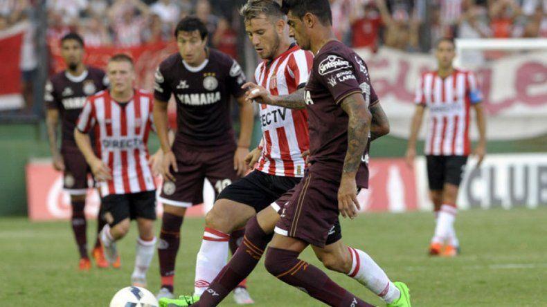 Román Martínez disputa el balón con Gastón Fernández.