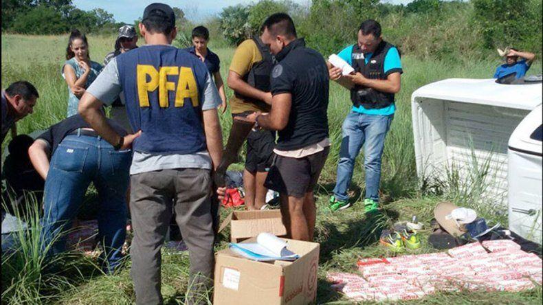 Personal de Policía Federal requisa la droga hallada en la camioneta que volcó.