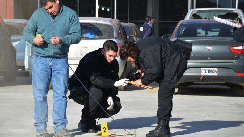 Peritos en Criminalística analizaron una mancha de sangre y recogieron un casquillo de bala en la explanada de estacionamiento del hipermercado mayorista.