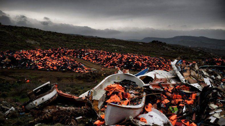 Botes dañados y miles de chalecos salvavidas usados por refugiados y migrantes durante su trayecto a través del mar Egeo