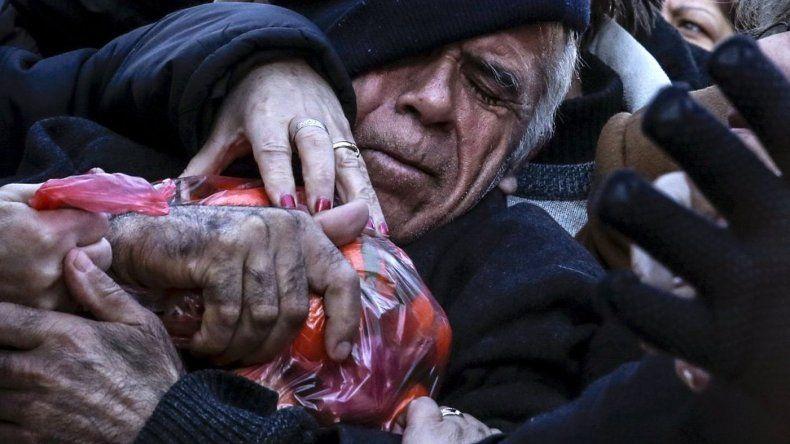 Un hombre agarra una bolsa de mandarinas entregadas por los agricultores durante una protesta por la propuesta del gobierno de reformar el sistema de pensiones del país