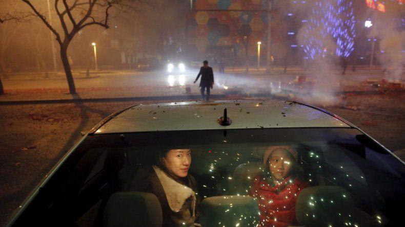 Una niña y una mujer esperan dentro del coche mientras estallan petardos y fuegos artificiales para celebrar el inicio del Año Nuevo en Pekín (China)