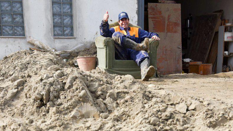 Pablo descansa un rato en un sillón que el alud dejó inservible.Los habitantes del Pueyrredón palean barro a la espera de máquinas.
