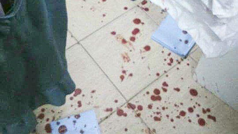 Manchas de sangre en el suelo de la tienda evidencian la brutalidad del ataque.