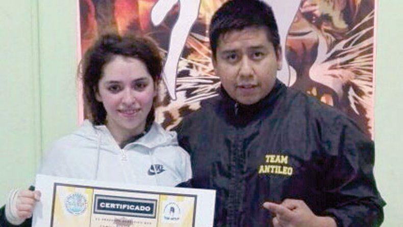 Camila Montenegro junto a Marcos Antileo y el diploma del cinto.