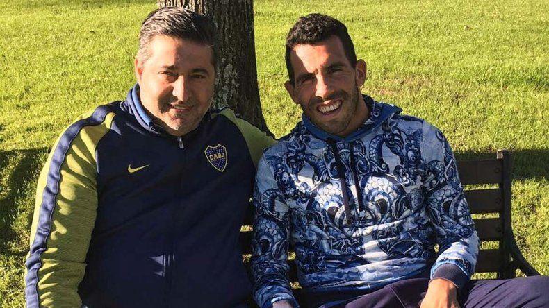 Daniel Angelici y el delantero Carlos Tevez sentados en un banco sobre una escenografía natural