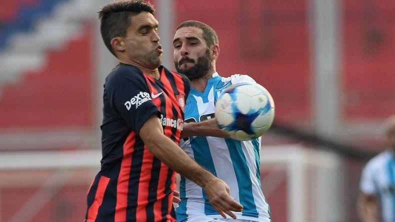 Matías Caruzzo disputa el balón con Lisandro López en el partido jugado ayer en cancha de San Lorenzo.