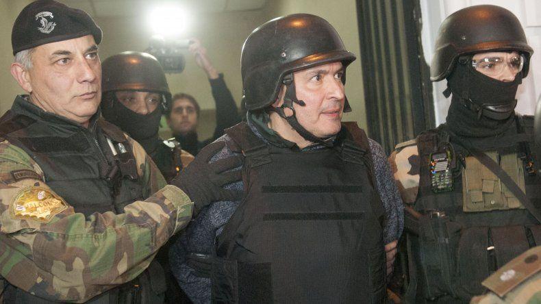 José López al ser trasladado a declarar bajo una fuerte custodia.