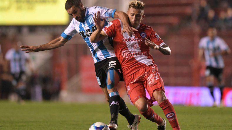 Lisandro López lucha por el balón con Gonzalo Piovi en el partido jugado anoche en La Paternal entre Argentinos y Racing.
