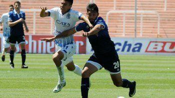 Omar Alderete se lleva el balón marcado por Guillermo Fernández en el partido que Godoy Cruz venció 3-0 a Gimnasia de La Plata en Mendoza.