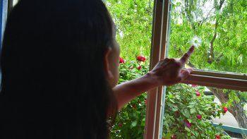 La mujer que fue víctima del atentado a balazos de su casa, en la que reside con tres chicos, muestra algunos de los impactos de los proyectiles de grueso calibre que atravesaron la ventana.