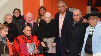 Acompañado por otros adultos mayores que residen en el Hogar de Ancianos Nuevo Amanecer, el Chango La Fuente sostiene el premio que le otorgó el comisionado de fomento de Cañadón Seco, Jorge Soloaga.