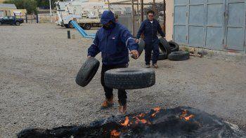 Dos operarios de SPSE arrojan cubiertas para alimentar la quema junto al portón de acceso al sector Energía.