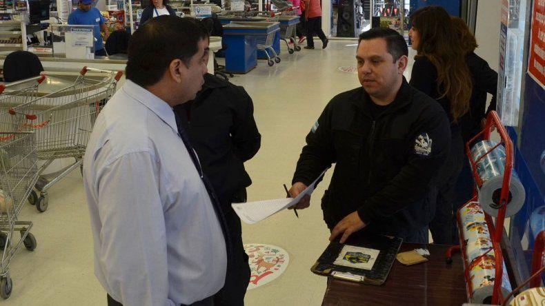 Un oficial de la Comisaría Seccional Segunda dialoga con el gerente de la sucursal del supermercado