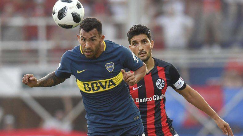 Carlos Tevez cabecea la pelota ante la mirada de Nicolás Blandi en el clásico entre San Lorenzo y Boca jugado anoche en el Nuevo Gasómetro.