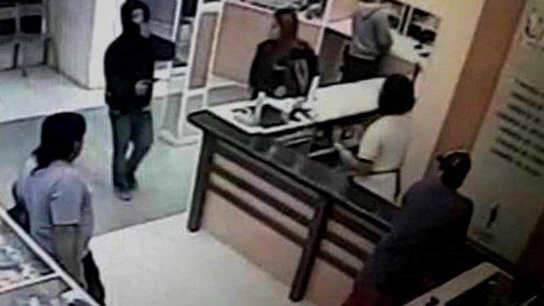 En esta imagen de video se observa a los dos individuos que ingresaron a la farmacia con sus rostros semi cubiertos con capuchas.