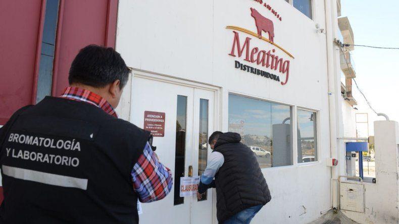 Los inspectores municipales colocan la faja de clausura en el local comercial.
