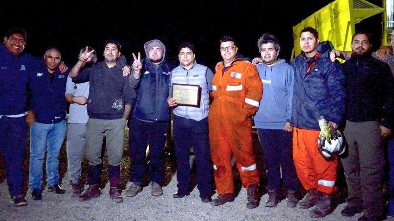 Sindicalistas y parte de los operarios del equipo perforador 601 de San Antonio Internacional muestran el certificado que acredita el récord operativo.