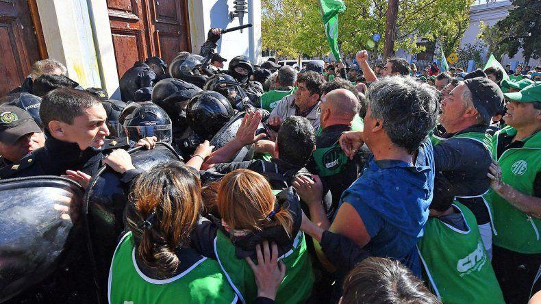 El forcejeo entre manifestantes y policías en las puertas de la Casa de Gobierno.