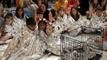 Niños envueltos con mantas para representar simbólicamente a los miles de niños separados de las familias en las fronteras, durmiendo en pisos y jaulas.