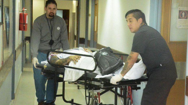 Personal policial del servicio de emergencias del Hospital Zonal trasladan al herido desde la sala de guardia al quirófano.