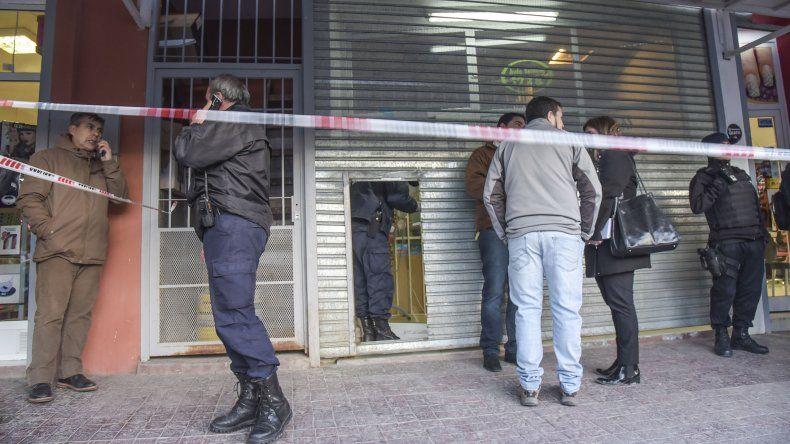 La Brigada de Investigaciones y la Policía Científica trabajan en la escena del crimen donde fue asesinada la comerciante.