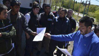 El delegado de los operarios transferidos de empresa, Carlos Páez, hace entrega a uno de sus compañeros la copia del convenio firmado en el organismo laboral provincial.