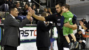 El capitán Diego Romero junto a un niño en brazos saluda a Eduardo Opezzo, el primer asistente técnico de Gimnasia y Esgrima.