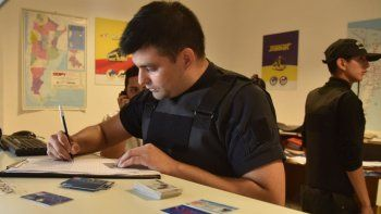 Un oficial de la policía toma registro de las tarjetas de crédito y de débito, como así también de numerosos DNI que se incautaron en la oficina que la empresa de colectivos posee en la terminal de ómnibus de Caleta Olivia.