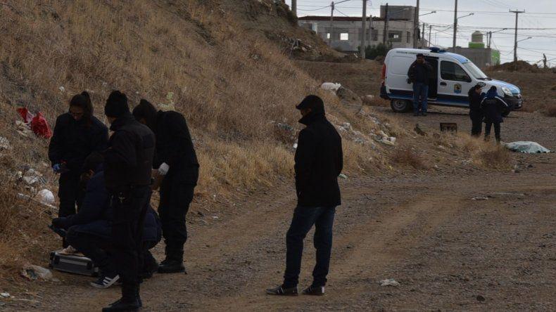 Personal de la División Criminalística inspecciona el lugar donde se halló la campera del occiso