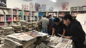 Estudiantes de la Escuela 796 trabajan con ejemplares de diario El Patagónico para crear su propio archivo hemerográfico en la biblioteca de su establecimiento.