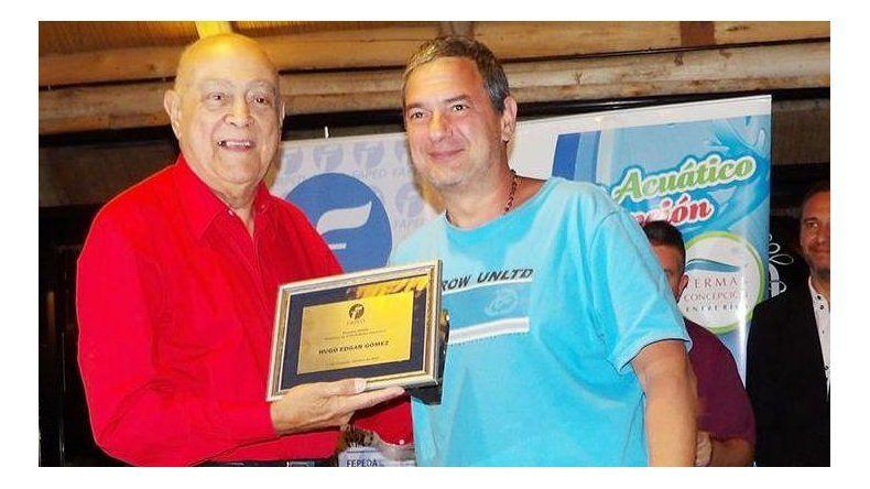 Hugo Gómez recibiendo una placa de parte de la Federación Argentina de Periodistas Deportivos.