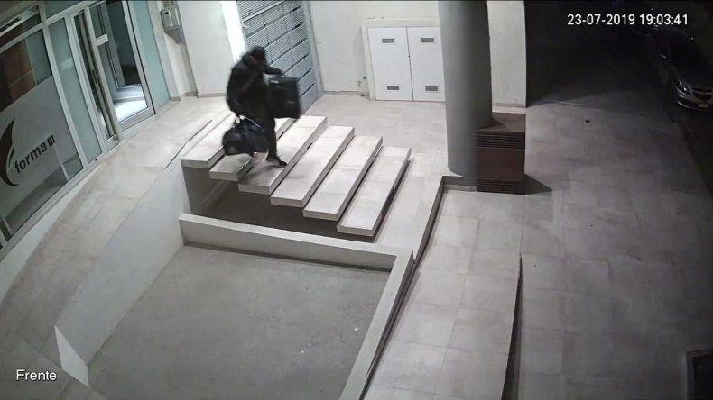 El momento en que el falso hombre araña sale por la puerta del edificio con lo robado.