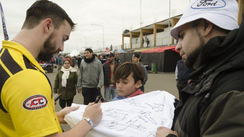 Gustavo Micheloud firmando autógrafos en la zona de boxes.