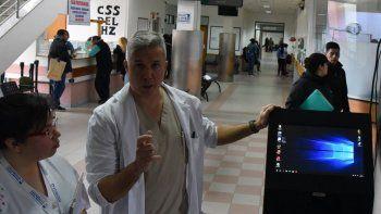 Daniel Covas, director general del Hospital Zonal de Caleta Olivia, acompañado por una empleada, muestra el dispositivo que se habilitó para obtener turnos de atención médica.
