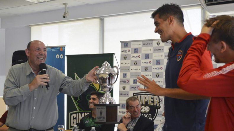 El periodista León Marcelo Schesterfeld intentando que Coco Mainoldi (Quimsa) agarre el trofeo para la foto.