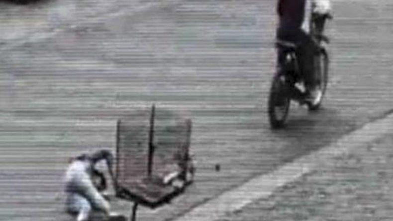 En esta imagen de video se observa cómo una mujer cae al suelo luego de que una pareja de motochorros le arrebatara con gran violencia una bolsa.