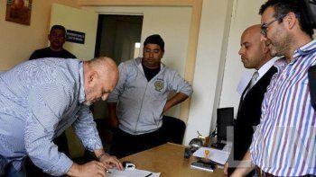 El referente local de Maxia SRL firma el acta acuerdo ante la presencia del director regional del Ministerio de Trabajo y el dirigente de la UTA, Oscar Contreras.